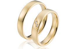 Gladde trouwringen van 14 krt goud  met 2 briljanten in de vrouwen ring