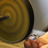 De goudsmid polijst de sieraden in zijn atelier