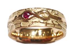 Gouden trouwring met eternity teken en een robijn
